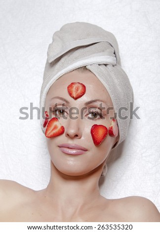beautiful young woman in towel with a strawberry cosmetic mask - stock photo