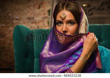 Beautiful young woman in traditional indian clothing with make-up and jewelry.