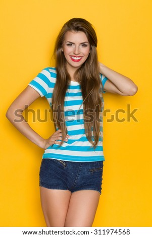 Beautiful young woman in turquoise striped shirt posing with hand on hip. Three quarter length studio shot on yellow background. - stock photo