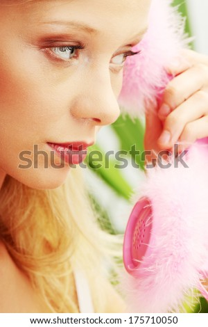 Beautiful young woman in underwear talking by pink phone - stock photo