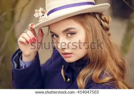Beautiful young woman in vintage purple dress and white hat walks in the park in early spring, close up portrait