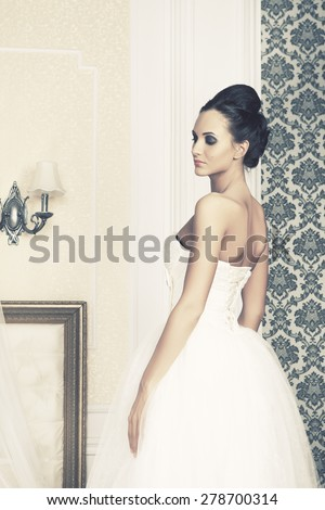 beautiful young woman in wedding dress, interior - stock photo