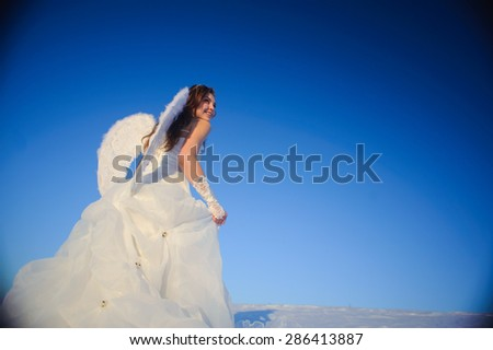 Beautiful young woman in wedding dress walking on snow field