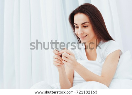 Beautiful young woman in white bed writing a message to a friend in the phone