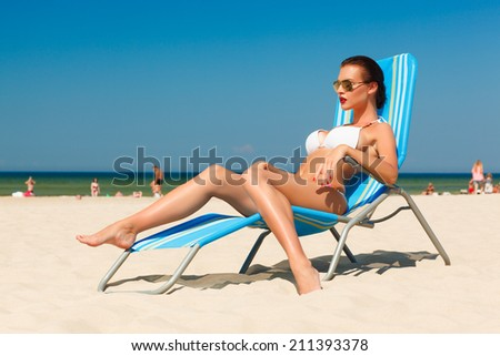beautiful young woman in white bikini and sunglasses relaxing in deck chair on the sand beach