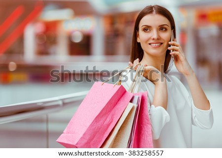 Beautiful young woman in white blouse talking on a mobile phone, holding shopping bags and smiling while standing in mall