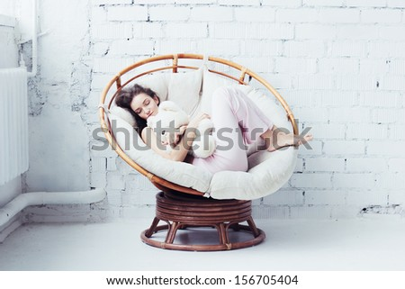 Beautiful young woman in white interior - stock photo