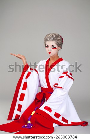 Beautiful young woman in white kimono dress on gray background  - stock photo