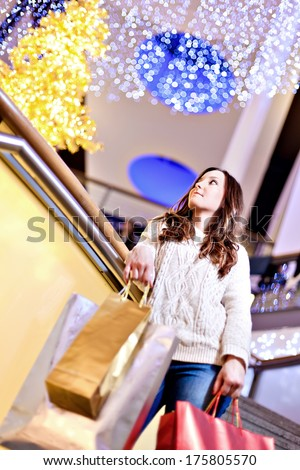 Beautiful young woman in white knitted sweater and blue jeans posing with shopping bags in mall during the Christmas sale. - stock photo
