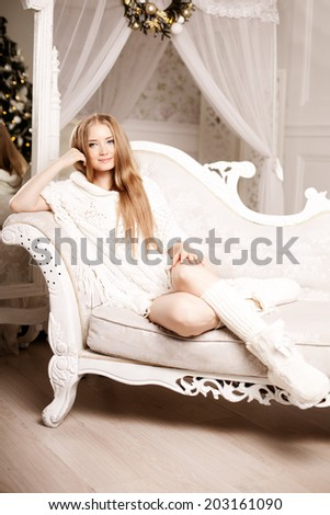 Beautiful young woman in white near the Christmas tree. Beautiful girl celebrates Christmas near the mirror - stock photo