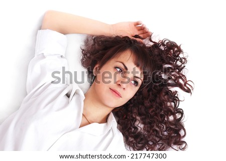 Beautiful young woman in white shirt lying on a bed - stock photo