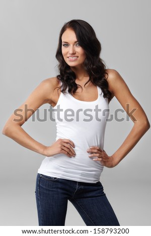 Beautiful young woman in white shirt on grey background - stock photo