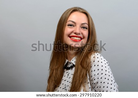 Beautiful young woman in white shirt posing with arms looking at camera against gray background.  - stock photo