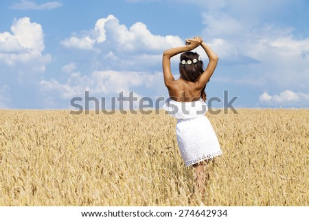Beautiful young woman in white summer dress in a wheat golden field - stock photo