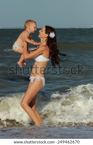 Beautiful young woman in white swimsuit holding a little boy go to the sea in a sunny summer day