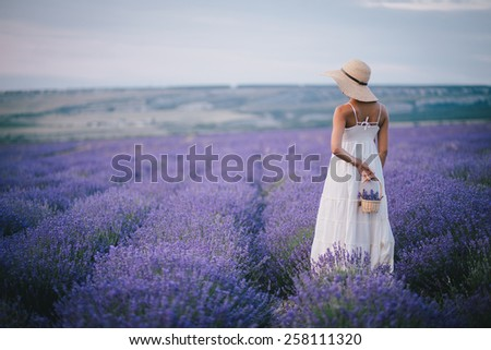Beautiful young woman in wicker hat and white dress posing in a lavender field with small wicker basket in her hand - stock photo