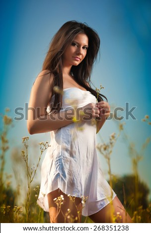 Beautiful young woman in wild flowers field on blue sky background. Portrait of attractive brunette girl with long hair relaxing in nature, outdoor shot. Lady in white short dress enjoying nature - stock photo
