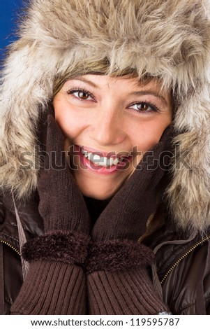 Beautiful young woman in winter clothes with a bright smile holding the hands to her face. Studio shot as a wintry close up portrait