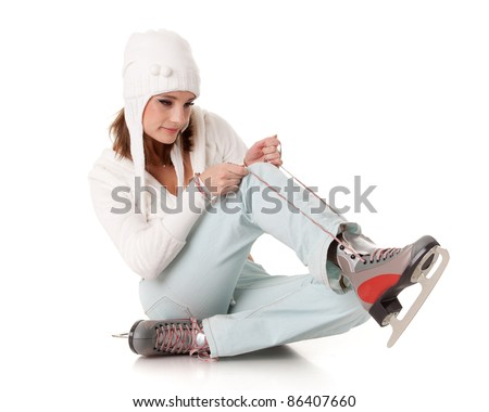 Beautiful young woman in winter clothes with skates  on a white background. Winter sports. - stock photo