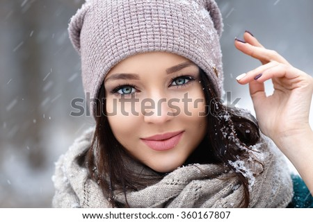 Beautiful young woman in wintertime outdoor, snowfall