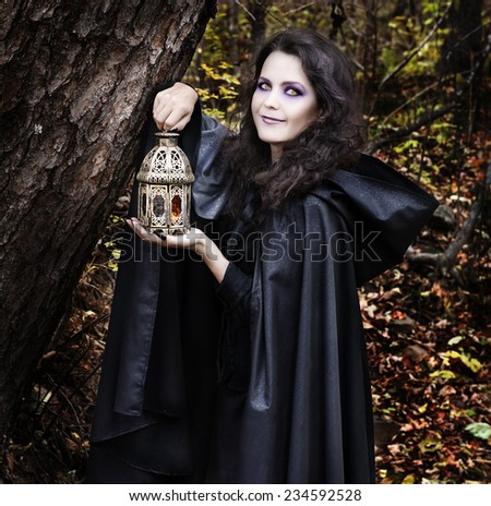 Beautiful young woman in witch costume with lantern for candle in the dark forest, Halloween image processed with filters - stock photo