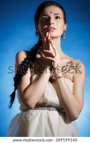 Beautiful young woman in with a long plait over blue background - stock photo
