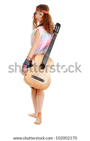 beautiful young woman in with an acoustic guitar walking and looking back. Isolated on white - stock photo