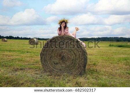 Beautiful young woman in wreath of cereal spikes on head lies on top of straw bale in field under blue cloudy sky - landscape