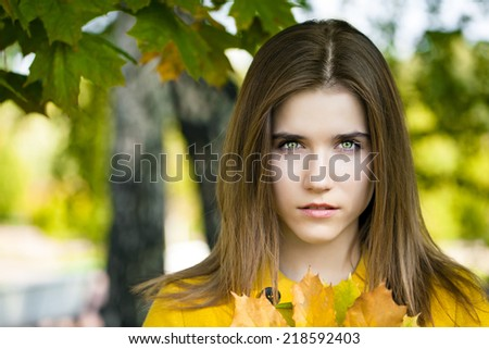 Beautiful young woman in yellow coat in autumn park