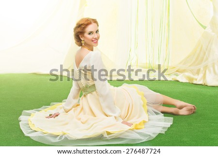 Beautiful young woman in yellow dress sitting on lawn - stock photo