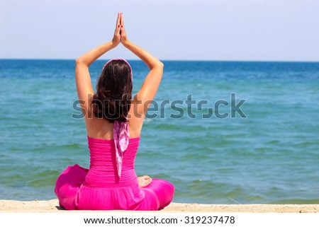 Beautiful young woman is doing exercises yoga on the seashore, Yoga exercises for the mind and body, Photography - stock photo