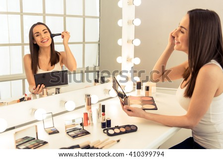 Beautiful young woman is doing makeup using a powder and smiling while looking at the mirror