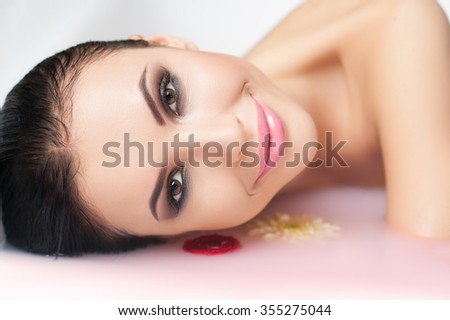 Beautiful young woman is enjoying purity. She is lying in water with flowers and smiling. The lady is looking forward with happiness - stock photo