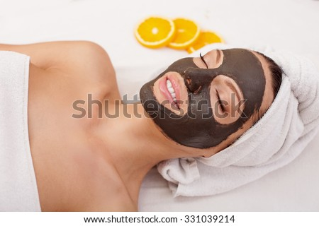 Beautiful young woman is getting facial chocolate mask at spa. She is lying with closed eyes. The girl is smiling