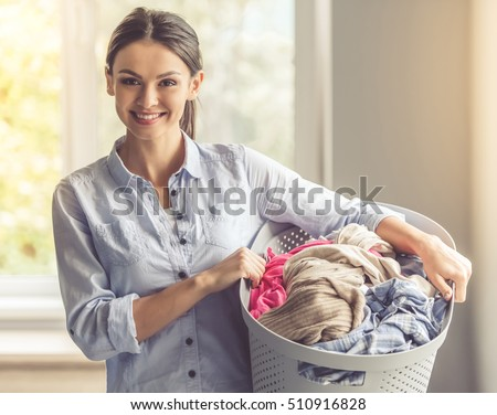 Beautiful young woman is holding a basin with laundry, looking at camera and smiling while standing at home