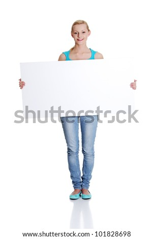Beautiful young woman is holding blank whiteboard sign. Isolated on white background. - stock photo