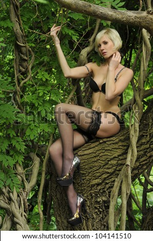 Beautiful young woman is leaning against a tree in the rain forest wearing Lingerie