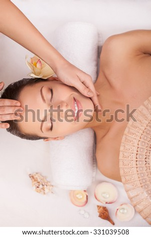 Beautiful young woman is lying and resting at spa. She is smiling with relaxation. Her eyes are closed. The masseuse is standing near her and massaging her head