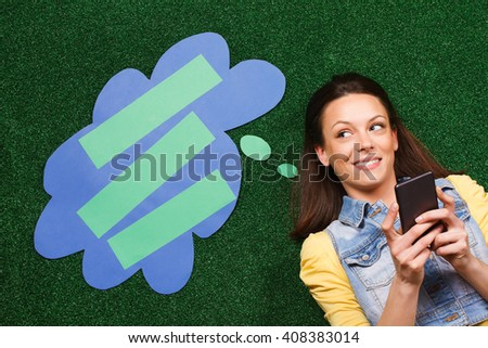 Beautiful young woman is lying on the grass and thinking about something while texting message with a thought bubble beside her head. Woman thinking with thought bubble while texting message - stock photo