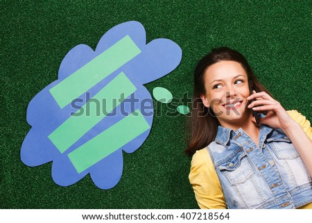 Beautiful young woman is lying on the grass and thinking about something while using phone with a thought bubble beside her head. Woman thinking with a thought bubble while using phone - stock photo