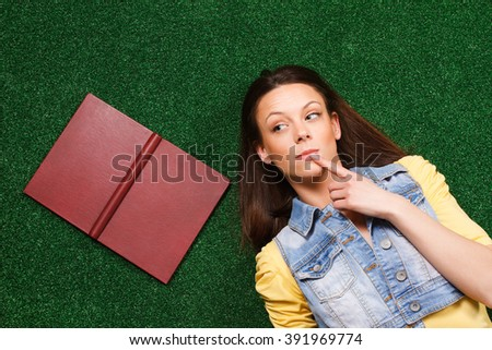 Beautiful young woman is lying on the grass and thinking about something with a book beside her.Woman thinking - stock photo