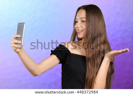 Beautiful young woman is making selfie photo with smartphone