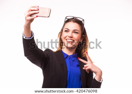 Beautiful young woman is making selfie photo with smartphone with victory gesture.