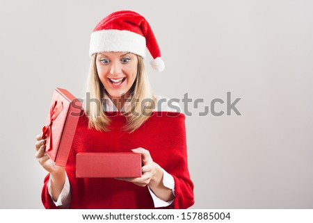 Beautiful young woman is opening Christmas present and she is very excited,Christmas gift