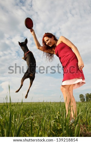 Beautiful young woman is playing on the field with dog - stock photo