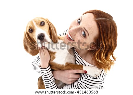 Beautiful young woman is playing with dog - stock photo
