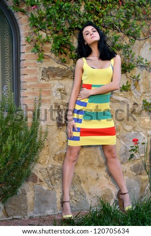 Beautiful young woman is posing on the old brick wall, Tuscan, Italy. Warm evening light - stock photo