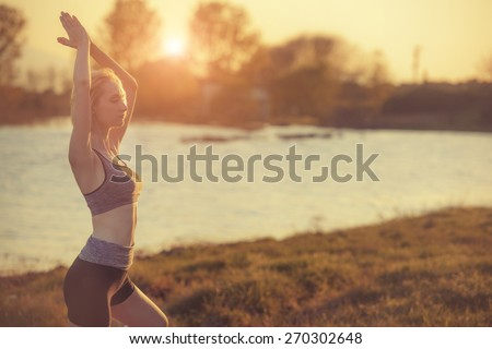 Beautiful young woman is practicing yoga near a lake