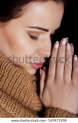 Beautiful young woman is praying. On black background. - stock photo
