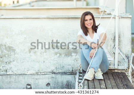Beautiful young woman is sitting on a wooden bench on a rooftop terrace,  looking at camera and smiling. Copy space - stock photo